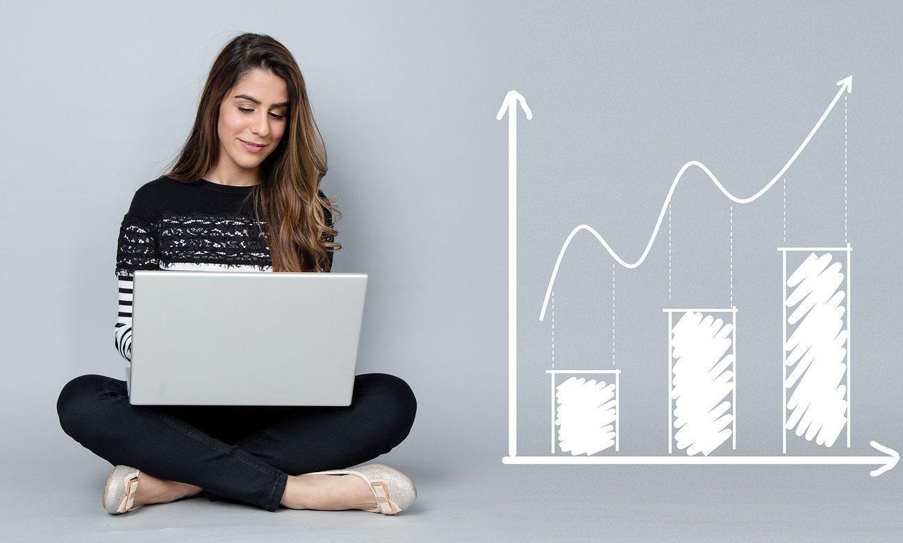 Imagem de uma mulher mexendo no computador, ao lado gráficos positivos para representar o sucesso da plataforma WebTV Corporativa.