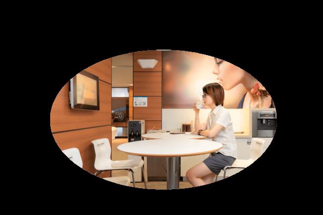 Mulher assistindo TV Corporativa de um escritório para ilustrar uma das opções de utilizar a plataforma de streaming WebTV.